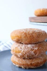 a close up of 3 cinnamon sugar donuts